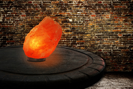Himalayan salt as a lamp on an old wooden table in front of a brickwall