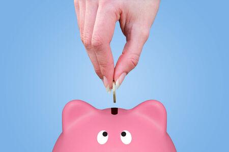 Female hand putting a coin in a piggy bank photo