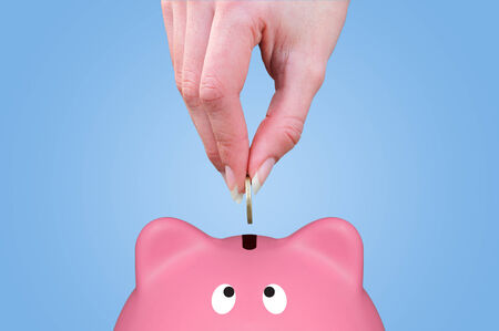 putting money in pocket: Female hand putting a coin in a piggy bank Stock Photo