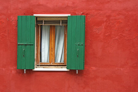 Old house red wall with green wooden window photo