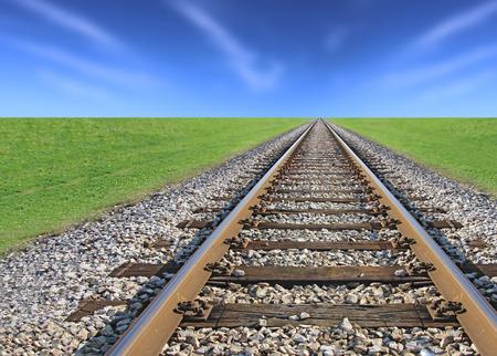 railway track: Railway track, green grass and blue sky on the horizon Stock Photo