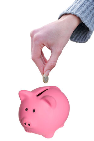 Female hand putting a coin euro in a piggy bank isolated on white with clipping path photo