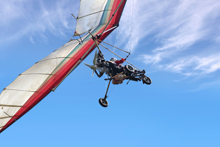 paraglide: The motorized hang glider in the blue sky