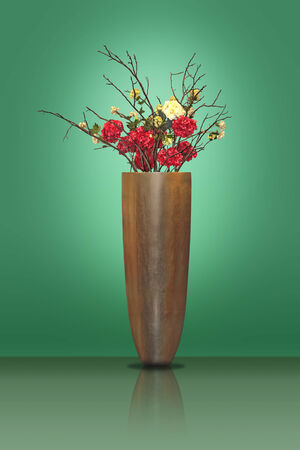 Red and yellow flowers in a large metal vase on a green background photo