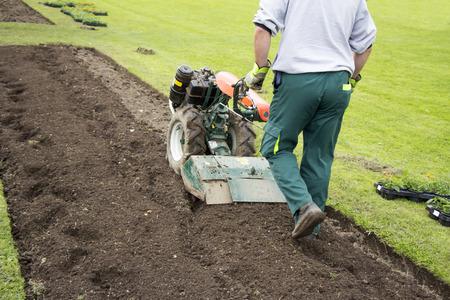 Man working in the garden with Garden Tiller  Standard-Bild