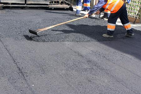 Asphalting 舗装機械道通り、修復中の労働者 写真素材