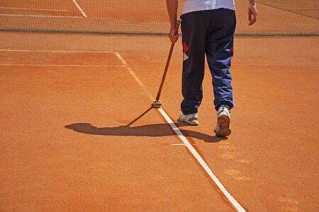tennis stadium: Cleaning the lines on a tennis court