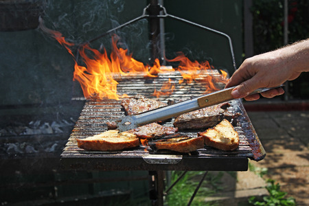 barbequing: Chef grilling pork meat on flame