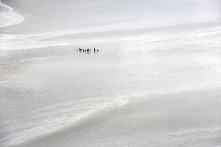 michel: Pilgrims walk across the sand during low tide, to the monastery Mont Saint Michel in France Stock Photo