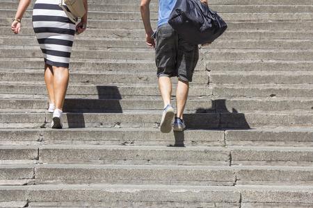 subir escaleras: Una escalada de la mujer y el hombre en las escaleras de hormigón Foto de archivo