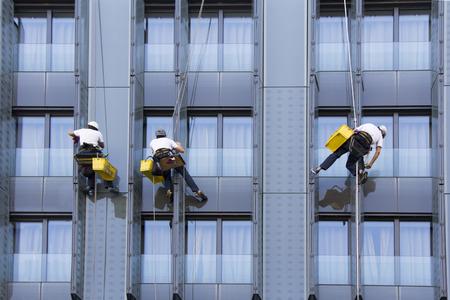 3 명의 등산객이 마천루의 유리창과 유리창을 닦는다.