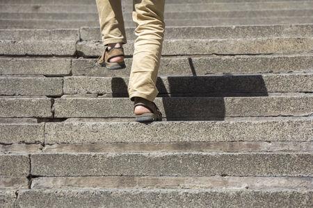 subir escaleras: El hombre se sube a una escalera de hormigón