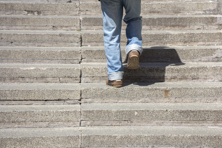 going up: Man climbs on a concrete stairs Stock Photo