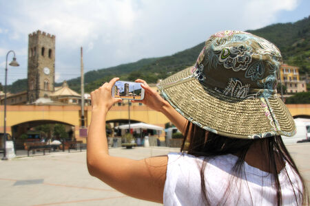 monterosso: A woman tourist, photographing with mobile phone, Monterosso, Cinque Terre, Italy