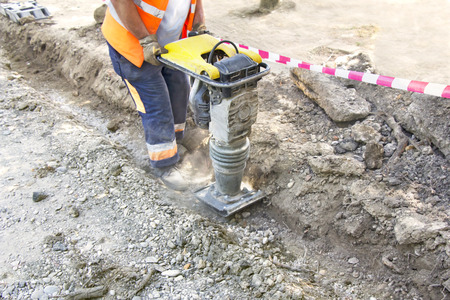 Worker uses compactor to firm soil at worksite Stock fotó - 29686084