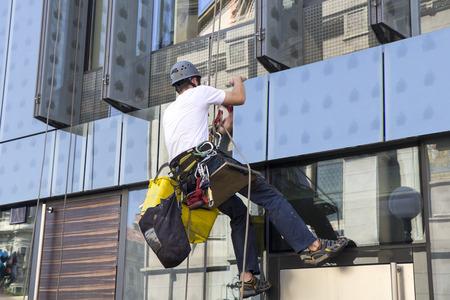 Climber wash windows and glass facade of the skyscraper