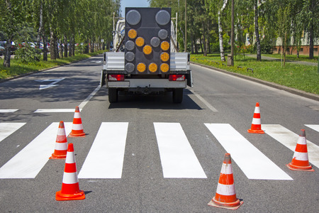 Road construction site with signs and orange road hazard cone photo