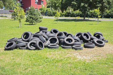 Old used tires stacked on the grass in the park  photo