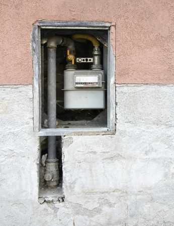 Pipes and gas meter on the wall of the house  photo