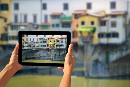 stone tablet: Girl taking pictures on a tablet Ponte Vecchio is a famous medieval bridge over the River Arno in Florence, Italy