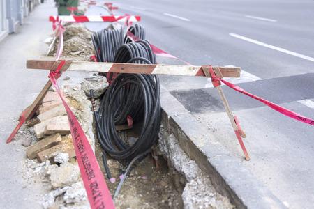 redes electricas: Excavación carretera en un sitio de construcción en conductos para el tendido de fibra óptica y el cable eléctrico