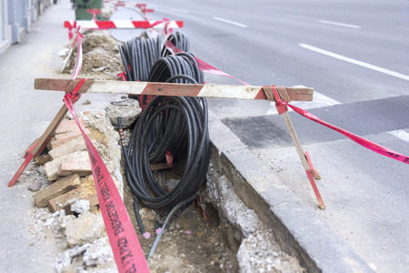 power cable: Road excavation at a construction site at conduits for the laying of fibre optic and electric cable