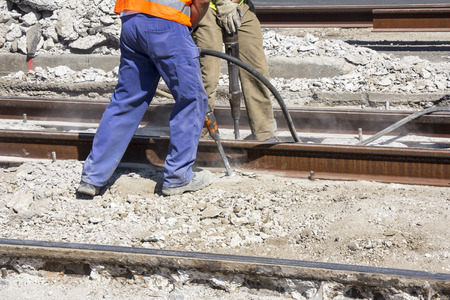 Two Workers with pneumatic hammer drill equipment breaking Concrete at construction site  photo