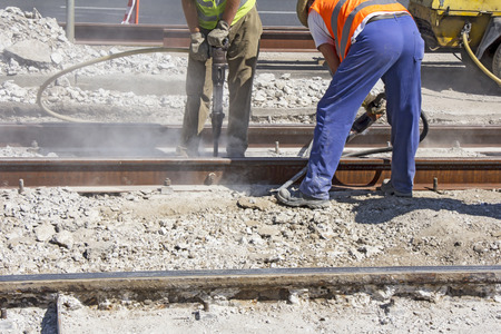 Two Workers with pneumatic hammer drill equipment breaking Concrete at construction site