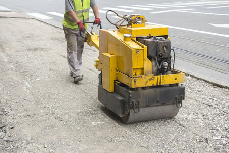 roller compactor: Worker driving Vibration roller compactor on repair pavement