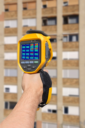 heat radiation: Hand with a Recording Heat Loss at the Residential Building With Infrared Thermal Camera