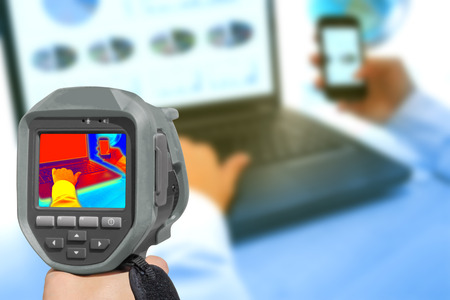 ir: Recording With Infrared Thermal Camera heat and radiation of Notebook and smartphones in the office Stock Photo