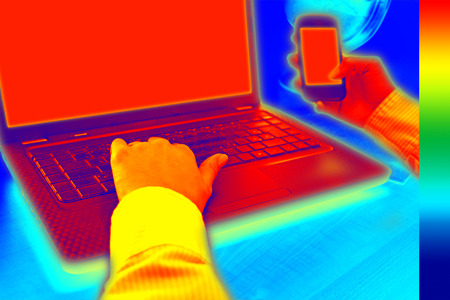 thermal: Infrared thermography image showing the heat and radiation of Notebook and smartphones in the office