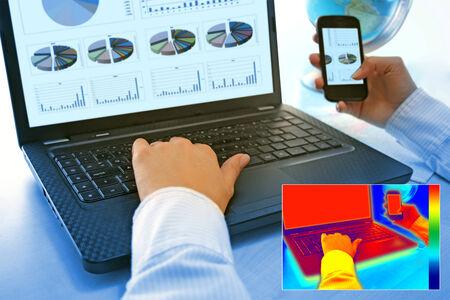 radiacion: Imagen termografía infrarroja que muestra el calor y la radiación de Notebook y smartphones en la oficina