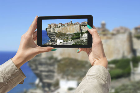stone tablet: Girl taking pictures on a tablet in Bonifacio, Corsica, France.