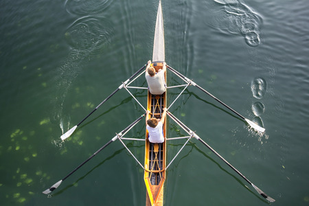 rower: Two young boys in a boat, paddles on the tranquil lake