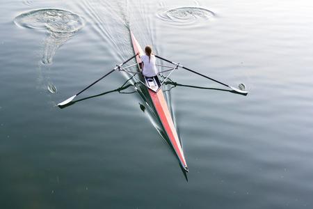 ボート、静かな湖上のパドルの若い女性