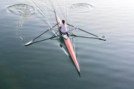 rower: A young woman in a boat, paddles on the tranquil lake  Stock Photo
