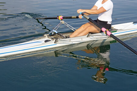 rowing: A young rower in a boat, paddles on the tranquil lake