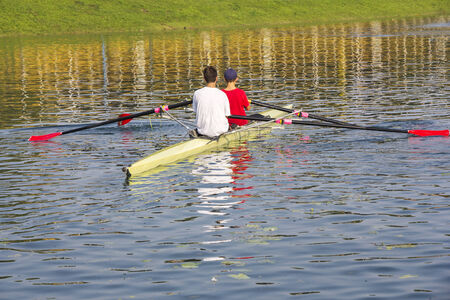 rower: Two rowers in a boat, paddles on the tranquil lake