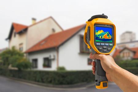 eficiencia energetica: Grabación de pérdida de calor en la casa con la cámara de infrarrojos térmica