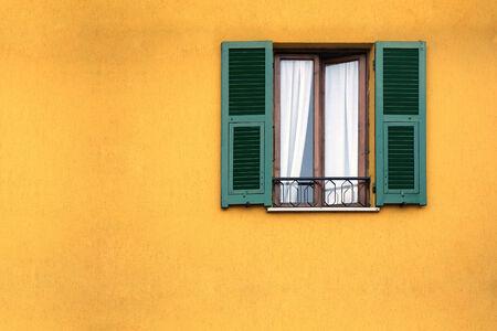 old house facade house: Green wooden window on the yellow facade