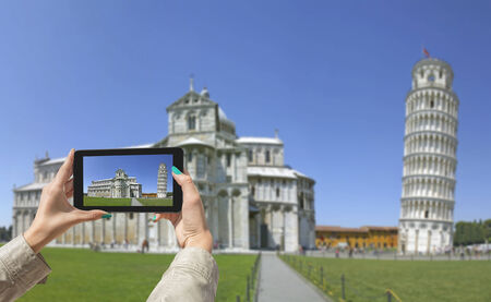 taken: Young girl traveling and taken pictures Leaning Tower in Pisa, with tablet