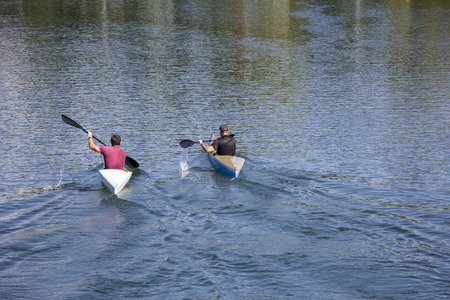 Two men in a canoes, rowing on the tranquil lake  photo