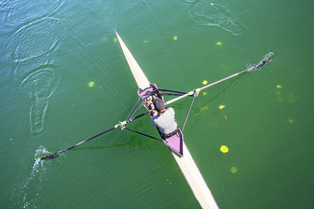 rower: The woman rower in a boat, rowing on the tranquil lake