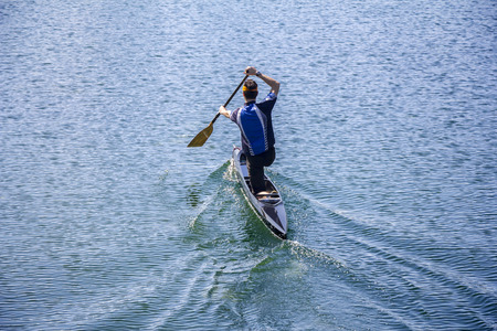 Man in a canoe, rowing on the tranquil lake