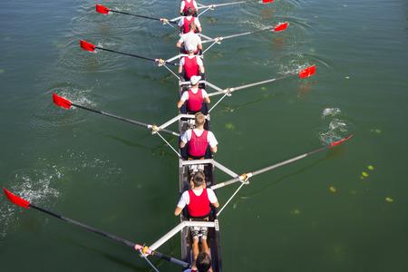 Roeiers in acht roeispaan roeiboten op het rustige meer