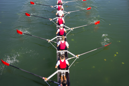 Rowers in eight-oar rowing boats on the tranquil lake photo