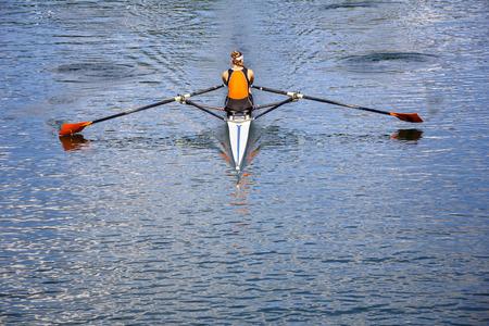 女性の漕ぎ手はボートで静かな湖で漕ぐ 写真素材