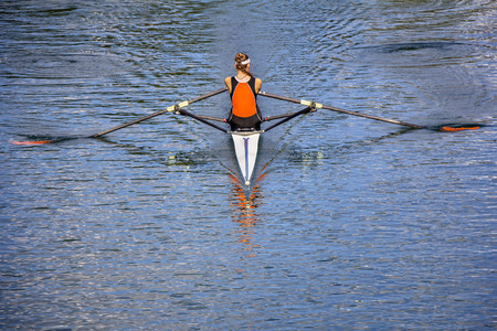 The woman rower in a boat, rowing on the tranquil lake photo