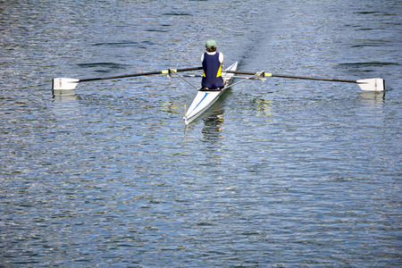 rowing: Rower in a boat, rowing on the tranquil lake